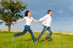 Happy couple running on a meadow Royalty Free Stock Photo