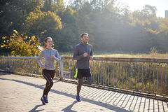 Happy couple running outdoors. Fitness, sport, people and jogging concept - happy couple running outdoors Stock Images