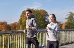 Happy couple running outdoors Stock Photo