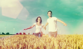 Happy couple running over grainfield Royalty Free Stock Photography