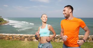 Happy couple running over sea or beach background Stock Image