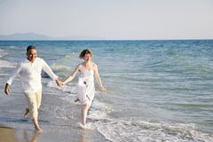 Happy couple running through sea waves on the beach Stock Photo