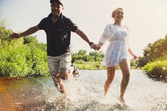 Happy couple running in shallow water. Stock Images