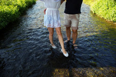 Happy couple running in shallow water. Royalty Free Stock Image