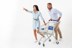 Happy couple running with a shopping cart. At the supermarket and pointing away isolated Stock Image
