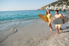 Happy couple running together while holding surfboards at beach Royalty Free Stock Photography