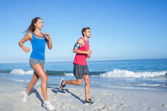 Happy couple running together beside the water Royalty Free Stock Photos