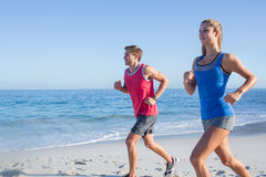 Happy couple running together beside the water Royalty Free Stock Photo