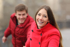 Happy couple running towards camera in winter Stock Images