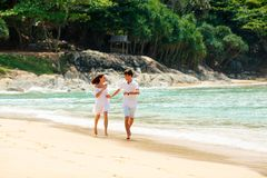 Happy couple running on tropical beach. Happy lovely caucasian couple running on tropical beach Royalty Free Stock Photography