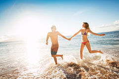 Happy couple running on a tropical beach. In the ocean at sunset Royalty Free Stock Photo