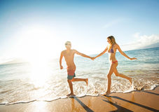 Happy couple running on a tropical beach Royalty Free Stock Photography