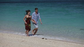 Happy Couple Running on Tropical Beach. Young couple holding hands running on a tropical beach, ocean, waves, they are happy.Love and the romantic on the stock video footage