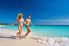Happy Couple Running Through Waves On Beach Holiday royalty free stock photo