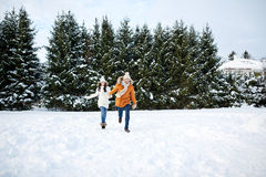 Happy couple running in winter snow Stock Images