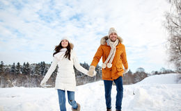 Happy couple running in winter snow Royalty Free Stock Images