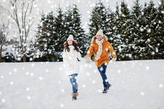 Happy couple running in winter snow Royalty Free Stock Photo