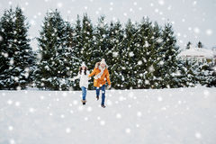 Happy couple running in winter snow Royalty Free Stock Image