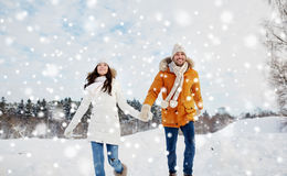 Happy couple running in winter snow Stock Image