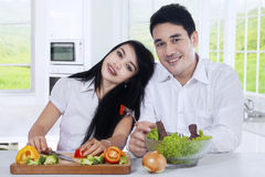 Happy couple with salad in the kitchen Stock Image