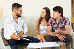 Happy couple and salesman talking. Happy couple and positive adult salesman talking cheerfully about purchase at home royalty free stock photos