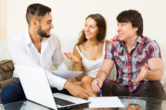 Happy couple and salesman talking. Happy couple and smiling salesman talking cheerfully about purchase at home royalty free stock image