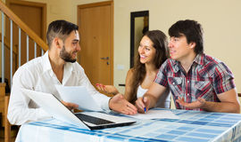 Happy couple and salesman talking Royalty Free Stock Photos