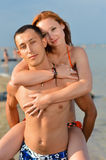 Happy couple on sandy beach having fun & looking at camera Stock Photos