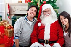 Happy couple with Santa Claus Stock Photo