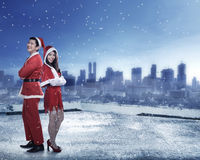 Happy couple in santa claus costume standing on the building rooftop. Christmas couple concept Stock Photo