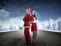 Happy couple in santa claus costume standing on the middle of the road Stock Photos