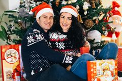 Happy couple with santa claus hats smiling royalty free stock photo