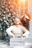 Happy Couple in Santa Hat with Christmas and New Year Gift at Home Royalty Free Stock Image