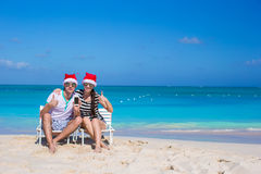 Happy couple in Santa hats enjoy beach vacation Stock Photography