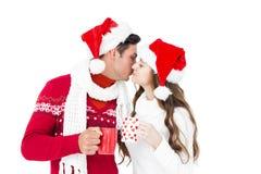 Happy couple with santa hats holding mug and kissing Stock Photo