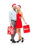 Happy couple in santa hats with red shopping bags Stock Photos