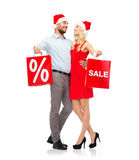 Happy couple in santa hats with red shopping bags Royalty Free Stock Photos