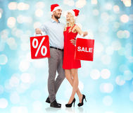 Happy couple in santa hats with red shopping bags Royalty Free Stock Images