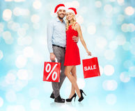 Happy couple in santa hats with red shopping bags Stock Photography