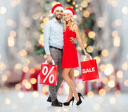 Happy couple in santa hats with red shopping bags Stock Photo