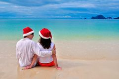 Happy couple in Santa hats relaxing on tropical sandy beach near sea, Christmas and New Year holiday vacation Royalty Free Stock Image