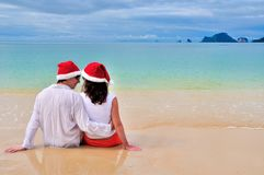 Happy couple in Santa hats relaxing on tropical sandy beach near sea, Christmas and New Year holiday vacation. Happy couple in Santa hats relaxing on tropical Royalty Free Stock Photography