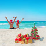 Happy couple in santa hats at sea beach near christmas tree Royalty Free Stock Photos