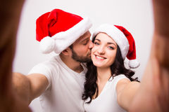 Happy couple in santa hats taking selfie picture from hands Stock Photo