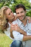 Happy couple sat outdoors Stock Photo