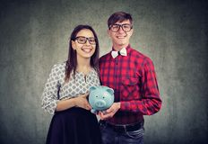 Happy couple with saved money in box stock images
