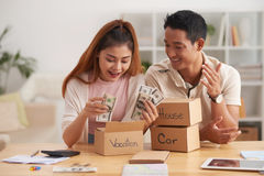 Happy Couple Saving Money. Portrait of young Asian couple putting money to piggy banks, saving  for house, car and vacation Royalty Free Stock Images