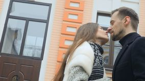 Happy couple says goodbye to each other. Happy couple stands outdoors near the building. The lovers says goodbye and pretty girl with long hair kisses her stock video
