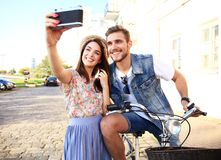 Happy couple on scooter making selfie photo on smartphone outdoors. Stock Images
