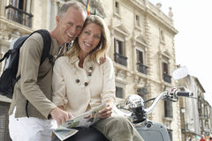 Happy Couple With Scooter Reading Map In Granada Stock Photography